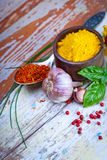 Colourful spices in bowls spilling onto an old aged scored woode Royalty Free Stock Photo