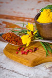 Colourful spices in bowls spilling onto an old aged scored woode Royalty Free Stock Photos