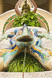 Colourful statue of lizard with flowing water. Colourful statue of lizard inlaid with beautiful staied glass with flowing water and plants around in Park Guell royalty free stock images