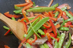Colourful stir-fry preparation. Colourful meat and vegetable stir-fry being cooked in black wok Royalty Free Stock Photography