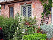 Colourful Stone Cottage and Garden, Galaxidi, Greece. A small neat and tidy stone restored house or cottage, with green shrubs in front garden, Galaxidi, Gulf of Royalty Free Stock Photos
