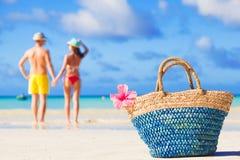 Colourful straw beach bag abd hugging honeymoon couple on background royalty free stock photos