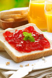 Colourful strawberry preserve on bread. Colourful vibrant red strawberry preserve topping a slice of fresh white bread on a plate with crumbs served with fresh Royalty Free Stock Photos