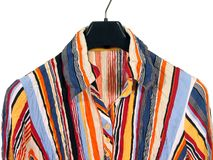 Colourful striped shirt on white background. Closeup of a stylish striped shirt on black hanger, isolated on white stock images