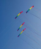 Colourful stunt kites. Four stacks of 12 stunt kites each in rainbow colours, on a blue sky background Stock Photos