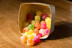 Colourful sugar sweets with licor inside in stiff fibers basket on the wooden table background. Colourful sugar sweets red green yellow and orange with licor stock images