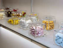 Colourful Sugared Almond in Glass Cubic Jars. Colourful Sugared Almond inside Glass Cubic Jars on White Shelf stock image