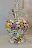 Colourful Sugared Almond in Glass Jars. Colourful Sugared Almond inside Glass Jars on White Shelf stock image