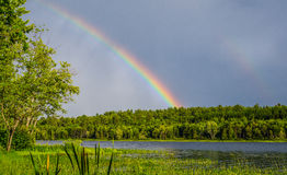 Colourful summer rainbow over an Eastern Ontario Lake after a rain storm. Royalty Free Stock Images