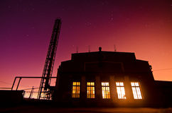 Colourful sunset behind an industrial building Stock Images