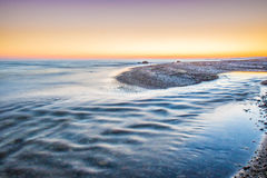 Colourful sunset over the sea with water reflection. Colourful and bright sunset of the island of Bornholm with a reflection in the blue calm water stock images