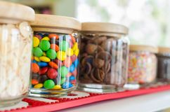 Colourful sweet candies in bottle on shelf in dessert store. stock image