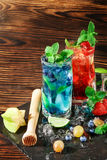 Colourful sweet cocktails with mint, lime, ice, berries on the wooden background. Refreshing summer beverages. Copy space. stock photography