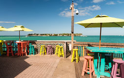 Colourful tables and chairs on a terrace along the ocean, holida Royalty Free Stock Photography