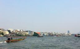 Colourful Tajlandzkiego ogonu zwiedzająca łódź na Chao Phraya rzece z pejzażu miejskiego tłem w wietrznym i chmurnym dniu obraz royalty free