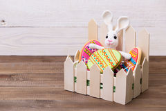 Colourful tasty Easter cookies and bunny on white wooden background Royalty Free Stock Photography