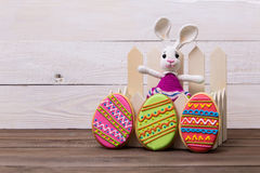 Colourful tasty Easter cookies and bunny on white wooden background Royalty Free Stock Photos
