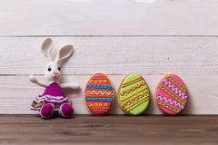 Colourful tasty Easter cookies and bunny on white wooden background Stock Images