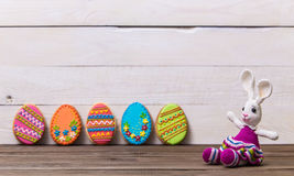Colourful tasty Easter cookies in a row and bunny on white wooden background Stock Image