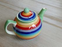 Colourful teapot on a wooden table Royalty Free Stock Images