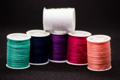 Colourful thread spools on a black background stock photography