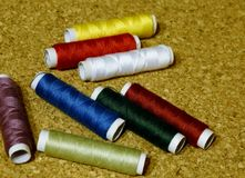 Colourful thread spools. Close up on cork background Royalty Free Stock Photos
