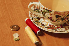 Colourful thread spools and tea cup. With colourful butterflies on a table Royalty Free Stock Image
