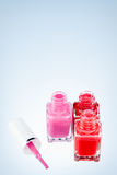 Colourful three!. Three open nail polish bottles of different colors on a white surface with one pink brush Stock Images