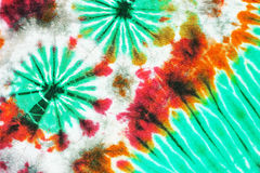 Colourful tie dyed pattern on cotton fabric background. Royalty Free Stock Images