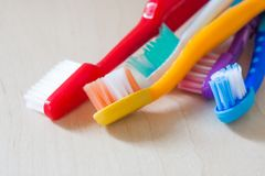 Colourful toothbrushes on a wooden surface. Colourful toothbrushes red, yellow, blue, white, violet on a wooden surface Stock Images
