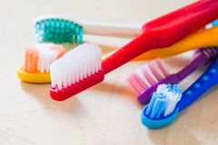 Colourful toothbrushes on a wooden surface. Colourful toothbrushes red, yellow, blue, white, violet on a wooden surface Royalty Free Stock Images