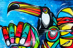 Colourful Toucan bird, urban art painting. Graffiti art, showing a Toucn tropical bird and hand. Brick Lane, London, UK Royalty Free Stock Photos