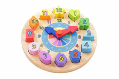 Colourful toy wooden clock. Child's toy wooden clock with colourful number shapes on a white background Stock Photography