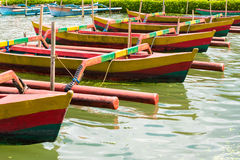Colourful traditional Balinese fishing boats. In line on the water Stock Images