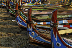 Colourful traditional boats. Perspective view of many colorful traditional Asian boats pulled up on the sand stock image