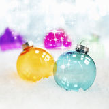 Colourful translucent glass baubles. Sparkling twinkling colourful translucent glass Christmas baubles in fresh winter snow with bokeh of soft white lights Royalty Free Stock Image