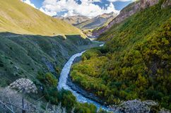 Colourful Truso Valley Gorge view vier river, forest and mountains behind in Kazbegi mountain range royalty free stock photo