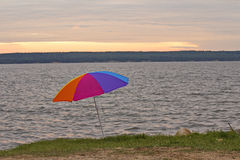 A colourful umbrella by a lake. With a setting sun and trees in the background Royalty Free Stock Image