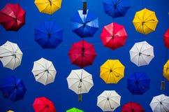 Colourful umbrellas. A collection of colourful umbrellas against a white sky Stock Photos