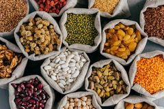 Colourful various beans in cloth sacks. Uncooked assorted legumes. Mulberry, buckwheat, pistache, raisins, almond, garbanzo,. Others. Healthy cereals royalty free stock image