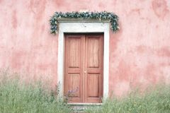 Church doors on a church in Corfu. A colourful view of wooden church doors surrounded buy tall grass and a garland of flowers Stock Photos