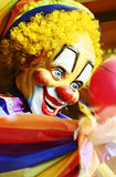Colourful weird spooky smiling clown at sideshow of fair Royalty Free Stock Image