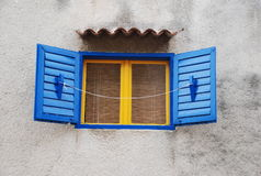 Colourful window. Blue and yellow window with shutters stock photo