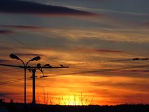 Colourful winter sunset in the town. Pure photo. No Photoshop correction. Orange, red, yellow, grey colours. Silhouette of street lamps and house roofs stock images