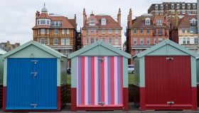 Colourful wooden beach huts on the sea front in Hove, Sussex, UK with blocks of flats behind. stock photo