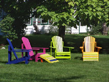 Colourful wooden lawn chairs. Arranged in front yard stock photo