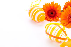 Colourful yellow decorated Easter eggs. Colourful yellow hand decorated traditional Easter eggs with stripes and polka dot patterns arranged with colourful Stock Photo