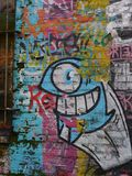 Colourfull graffiti wall in London. Graffiti on a wall in London UK depicting an one eye monster Stock Image