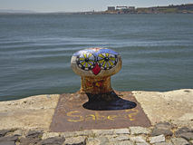 Colourfull mooring bollard with painted bird face on the shore of river Tejo, Lisbon stock photos
