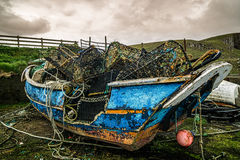 Colourfull old fisherman boat on the shore of Scotland. Old boat using as a storage for the traps with dramatic clouds Royalty Free Stock Image